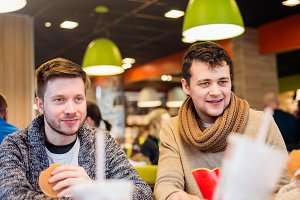 Two men eating out in fast food restaurant, talking