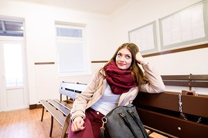 Beautiful young woman traveling, sitting in bus waiting room