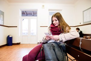 Woman with smartphone traveling, sitting in bus waiting room