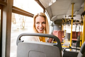 Beautiful young woman traveling by bus, having fun