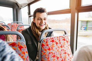 Handsome young man traveling by bus, having fun