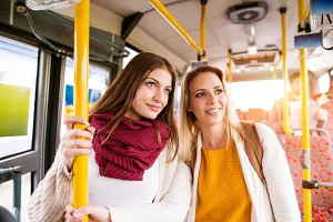 Beautiful young women traveling by bus, having fun