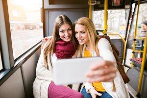 Beautiful young women traveling by bus, taking selfie
