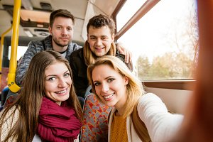 Group of young people traveling by bus, taking selfie