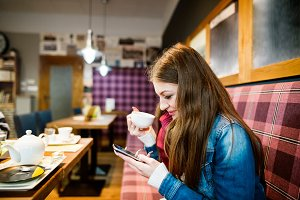 Woman with smart phone in cafe, texting