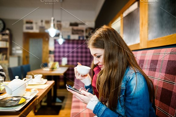 Woman With Smart Phone In Cafe Texting