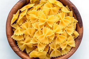 farfalle macaroni pasta in wooden bowl on white isolated background in the center close-up with top.