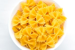 farfalle macaroni pasta in white bowl on white isolated background in the center close-up with top.