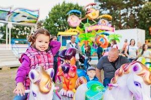 Little girl enjoying ride at fun fair, amusement park