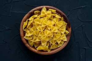 farfalle macaroni pasta in a wooden bowl on a black textured background, in the center close-up from the top.