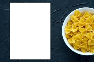 farfalle macaroni Pasta in a white bowl on a black textured background from the side. Close-up with the top. White space for text and ideas.