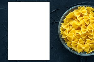 farfalle macaroni Pasta in a glass cup on a black textured background from the side. Close-up with the top. White space for text and ideas.
