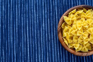 farfalle macaroni pasta in a wooden bowl on a striped white blue cloth background with a side. Close-up with the top. With space for text.