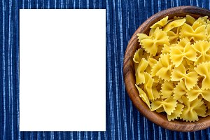 farfalle macaroni pasta in a wooden bowl on a striped white blue cloth background with a side. Close-up with the top. White space for text and ideas.