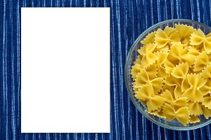 farfalle macaroni Pasta in a glass cup on a striped white blue cloth background with a side. Close-up with the top. White space for text and ideas.