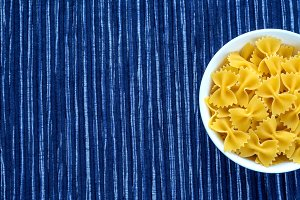 farfalle macaroni pasta in a white bowl on a striped white blue cloth background with a side. Close-up with the top. With space for text.