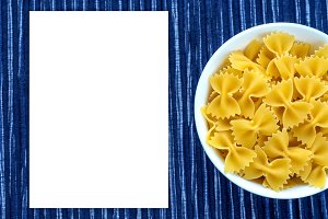 farfalle macaroni pasta in a white bowl on a striped white blue cloth background with a side. Close-up with the top. White space for text and ideas.