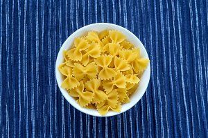 farfalle macaroni Pasta in a white cup on a striped white blue cloth background in the center. Close-up with the top.