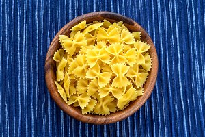 farfalle macaroni pasta in a wooden bowl on a striped white blue cloth background in the center. Close-up with the top.
