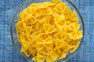 farfalle macaroni Pasta in a glass bowl on a blue knitted background in the center. Close-up with the top.