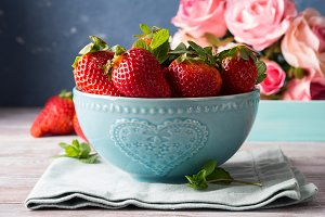 Strawberries in bowl with heart and roses