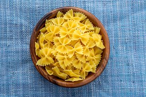 farfalle macaroni pasta in a wooden bowl on a blue knitted background in the center. Close-up with the top.