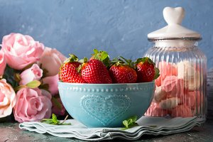 Strawberries in bowl with heart and meringues