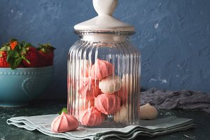 Pink and white meringues in glass jar with heart