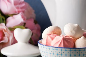 Pink and white meringues in bowl and flowers