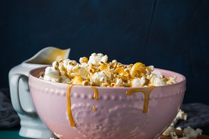Popcorn with caramel in bowl on dark background