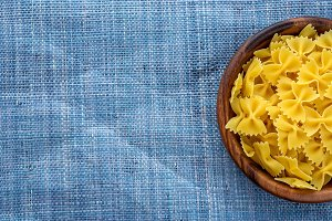 farfalle macaroni pasta in wooden bowl on blue knitted textured background with side. Close-up with the top. With space for text.