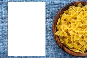 farfalle macaroni pasta in wooden bowl on blue knitted textured background with side. Close-up with the top. White space for text and ideas.
