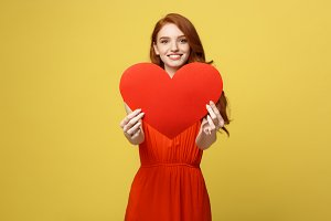 Portrait happy woman holding a heart symbol on yellow background