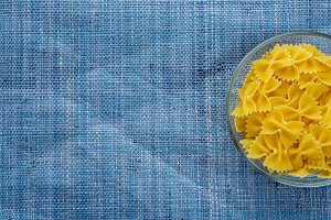 farfalle macaroni Pasta in glass cup on blue knitted textured background with side. Close-up with the top. With space for text.