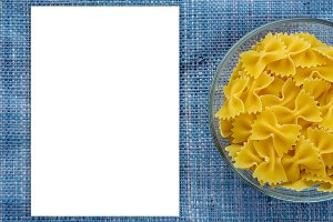 farfalle macaroni Pasta in glass cup on blue knitted textured background with side. Close-up with the top. White space for text and ideas.