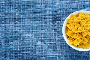 farfalle macaroni pasta in a white bowl on a blue knitted textured background with a side. Close-up with the top. With space for text.