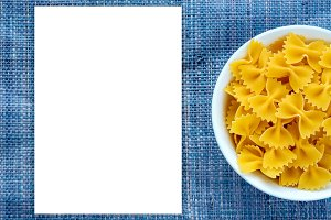 farfalle macaroni pasta in a white bowl on a blue knitted textured background with a side. Close-up with the top. White space for text and ideas.