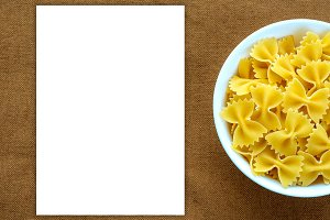 farfalle macaroni pasta in a white bowl on a brown rustic background texture with a side. Close-up with the top. White space for text and ideas.