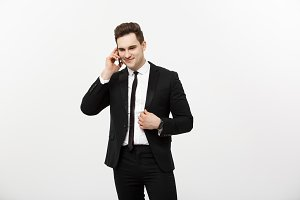 Handsome businessman in suit speaking on the phone over isolated white background.