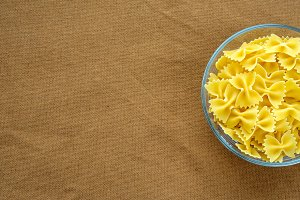 farfalle macaroni Pasta in a glass cup on a brown suburban background texture with a side. Close-up with the top. With space for text.