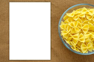 farfalle macaroni Pasta in a glass cup on a brown suburban background texture with a side. Close-up with the top. White space for text and ideas.