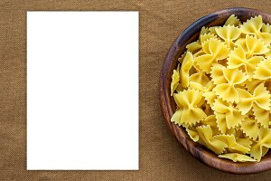 farfalle macaroni pasta in a wooden bowl on a brown rustic background texture with a side. Close-up with the top. White space for text and ideas.