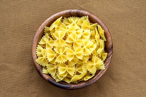 farfalle macaroni pasta in a wooden bowl on a brown rustic texture background, in the center close-up from the top.