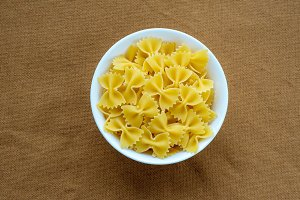 farfalle macaroni pasta in a white cup on a brown rustic texture background, in the center close-up from the top.