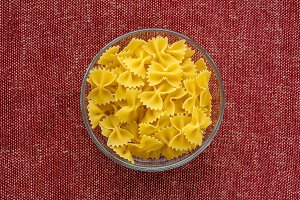 farfalle macaroni pasta in a glass bowl on a red brown rustic texture background, in the center close-up from the top.
