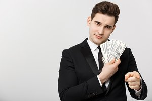 Portrait of businessman showing money and pointing fingers isolated over white background