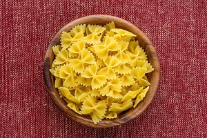farfalle macaroni pasta in a wooden bowl on a red brown rustic texture background, in the center close-up from the top.