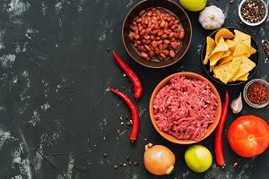 Ingredients for Mexican dishes chili con carne. Black concrete background, top view, space for text.