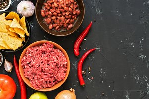 Ingredients for cooking Mexican chili concarne dishes on a black concrete background, top view. Copy space.