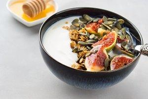 Healthy breakfast yogurt bowl with granola and fig